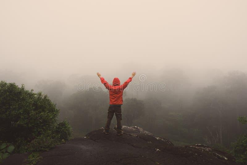 Las manos aumentadas hombre del viajero que se colocan en las montañas del acantilado se aventuran vacaciones de verano del conce fotografía de archivo