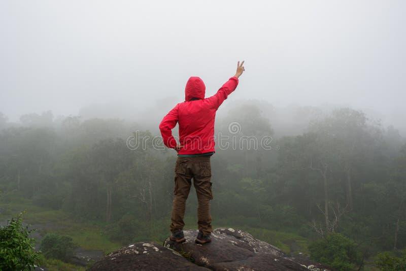 Las manos aumentadas hombre del viajero que se colocan en las montañas del acantilado se aventuran vacaciones de verano del conce foto de archivo libre de regalías