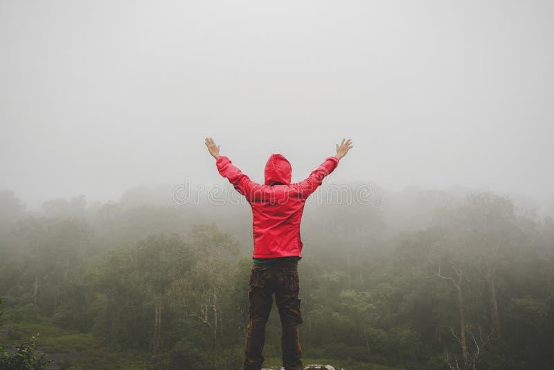 Las manos aumentadas hombre del viajero que se colocan en las montañas del acantilado se aventuran vacaciones de verano del conce fotografía de archivo libre de regalías