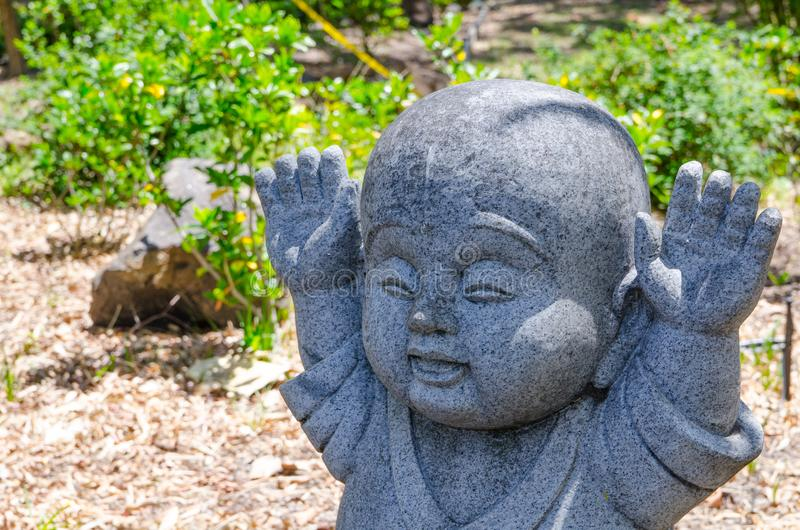 Las manos aumentadas suben el movimiento de Jizo poca estatua de piedra de Buda fotografía de archivo libre de regalías