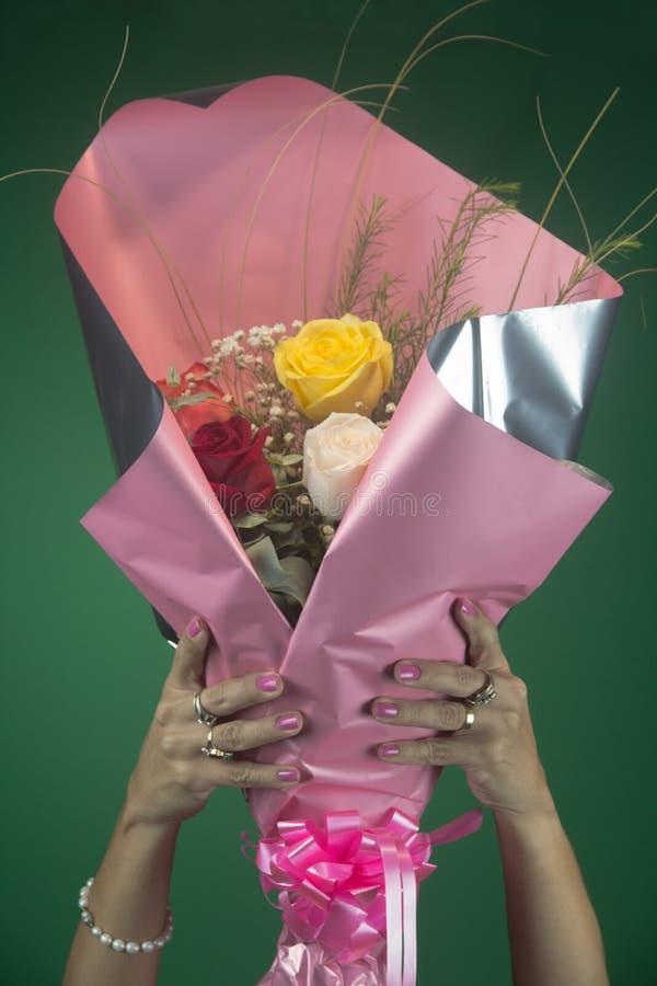 Las manos aumentan un ramo de rosas con el embalaje fotos de archivo