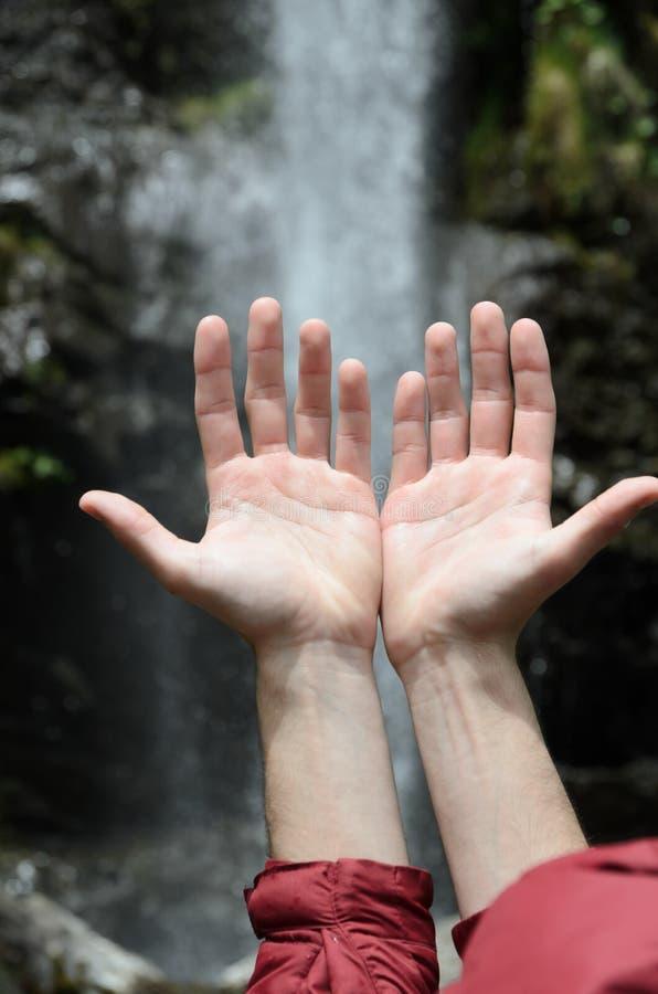 Las manos aumentaron hacia una cascada foto de archivo libre de regalías