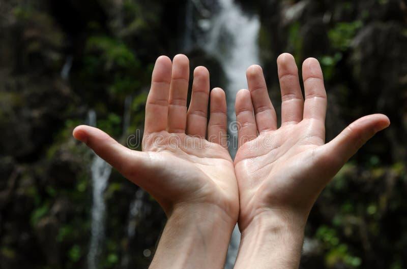 Las manos aumentaron hacia una cascada imagenes de archivo