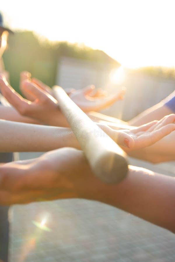 Las manos borrosas sostienen un palillo borroso, de madera actividad teambuilding con un palillo y las manos colegas rayos de la  foto de archivo libre de regalías