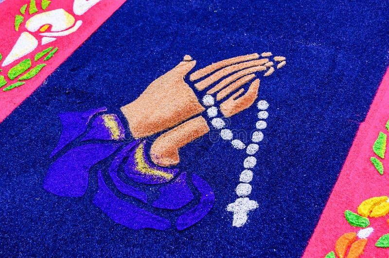 Las manos con el rosario gotean en la alfombra de la semana santa, Antigua, Guatemala fotos de archivo libres de regalías