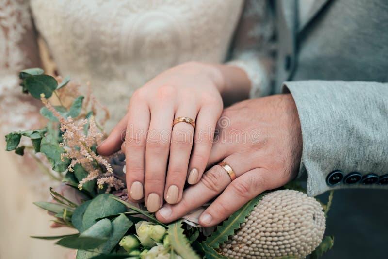 Las manos con los anillos de la novia y del novio est?n mintiendo en el primer del ramo imágenes de archivo libres de regalías