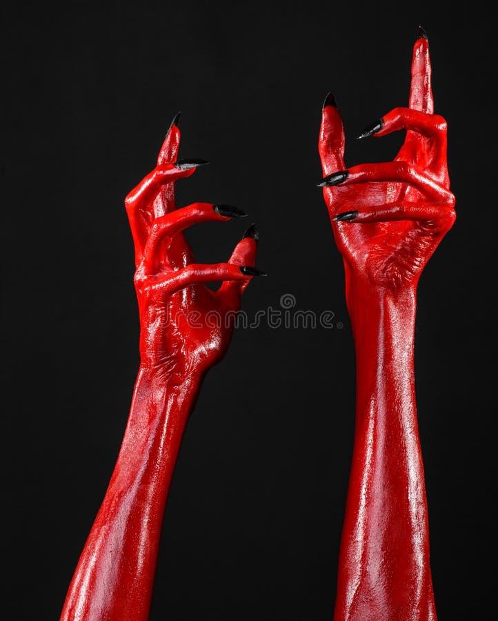 Las manos con los clavos negros, manos rojas de Satanás, tema del diablo rojo de Halloween, en un fondo negro, aislado imagenes de archivo
