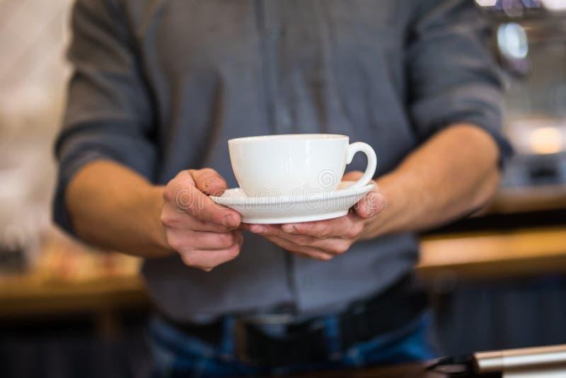 Las manos de Barista preparan capuchino en su cafeter?a Cierre para arriba fotos de archivo