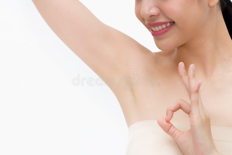 Las manos de elevación de la mujer asiática joven hasta muestran apagado los axilas o las axilas y el donante limpios e higiénico fotos de archivo