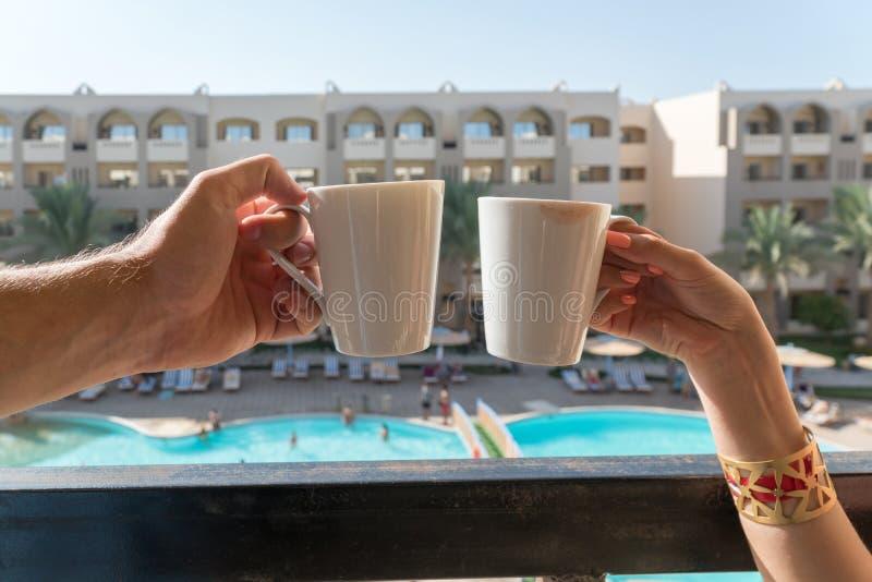 Las manos de hombres y de mujeres mantienen las tazas de café en el balcón el fondo del hotel, donde están VI los edificios y la  fotos de archivo libres de regalías