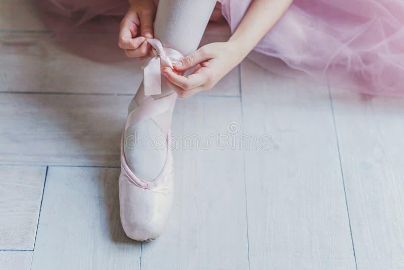 Las manos de la bailarina ponen los zapatos del pointe en la pierna en clase de danza imagenes de archivo