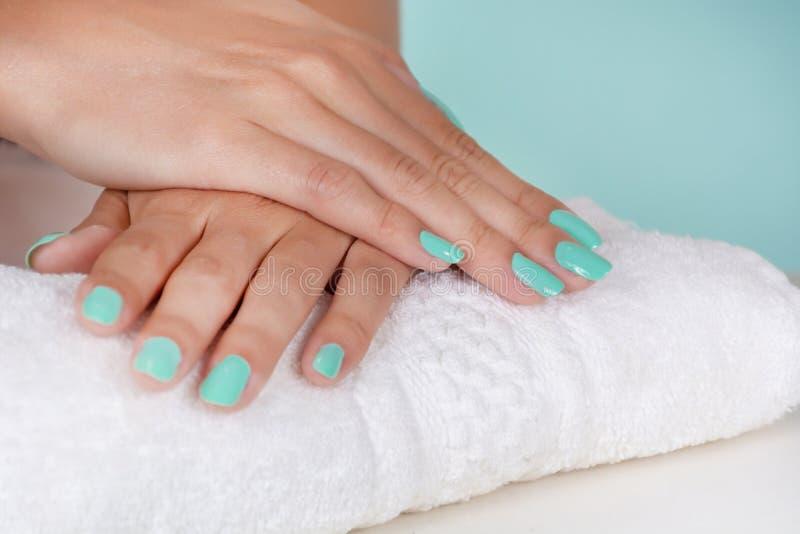 Las manos de la chica joven con los clavos de un color de la turquesa pulen en una toalla blanca en el escritorio aislado en fond fotografía de archivo libre de regalías