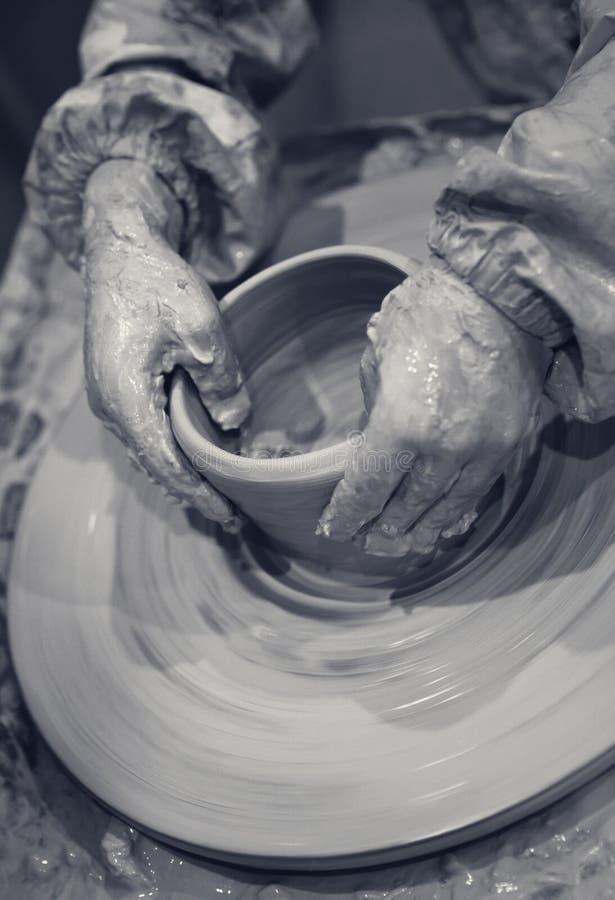 Las manos de la chica joven en vías de la fabricación de la loza en la cerámica ruedan imágenes de archivo libres de regalías