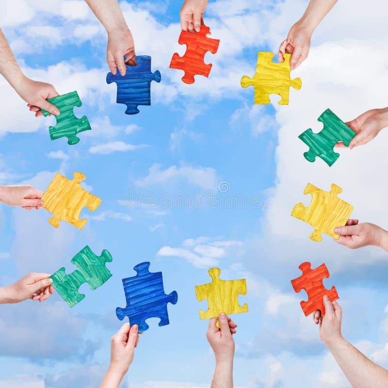 Las manos de la gente con rompecabezas juntan las piezas con el cielo azul fotografía de archivo libre de regalías