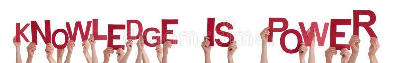 Las manos de la gente que llevan a cabo conocimiento rojo de la palabra son poder fotos de archivo
