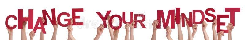 Las manos de la gente que llevan a cabo palabra roja cambian su modo de pensar imagen de archivo libre de regalías
