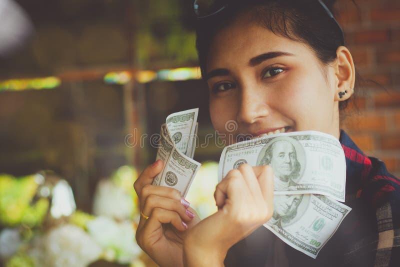 Las manos de la gente que sostienen billetes de banco de los dólares americanos con feliz imágenes de archivo libres de regalías
