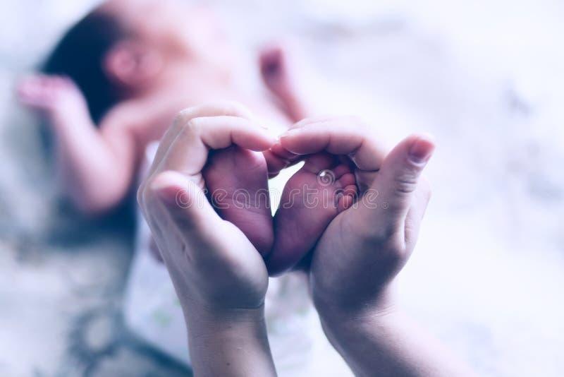 Las manos de la madre guardan al pequeño bebé de los pies Familia feliz amistosa fotografía de archivo libre de regalías