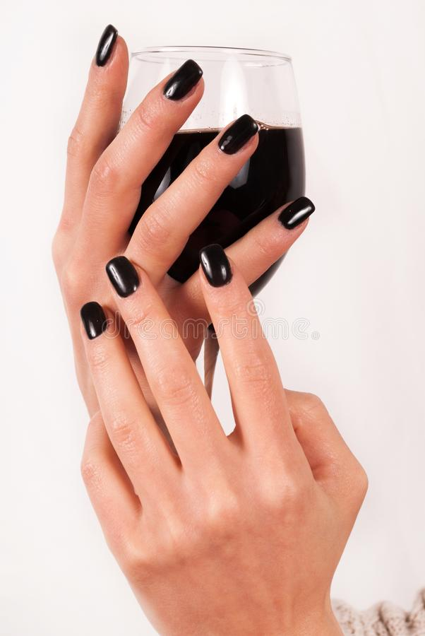 Las manos de la muchacha con el clavo negro sostienen la copa de vino con el vino rojo en el fondo blanco imagen de archivo libre de regalías