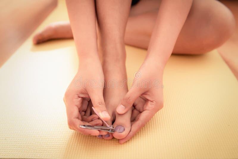 Las manos de la mujer del primer están cortando sus clavos de los pies en dormitorio imagen de archivo libre de regalías
