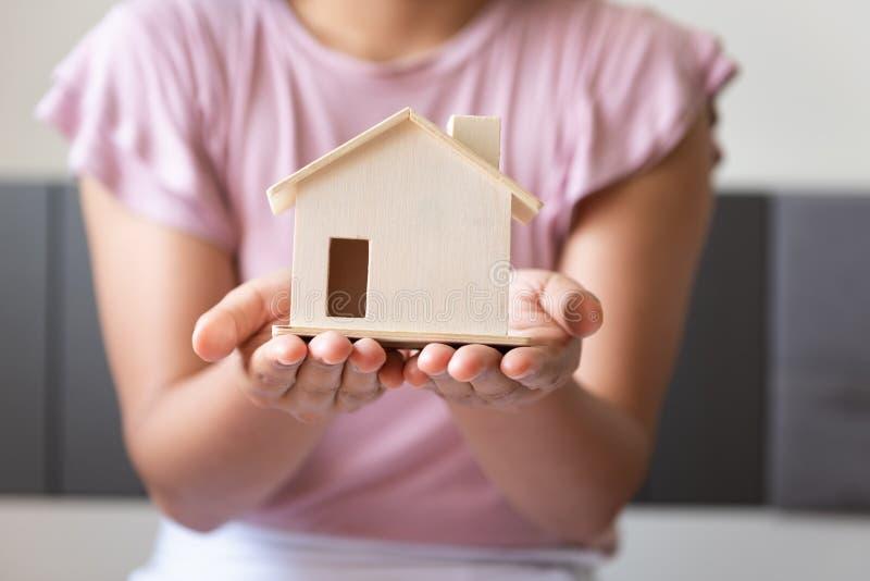 Las manos de la mujer del primer están llevando a cabo el modelo de la casa, la propiedad y el concepto de Real Estate de la inve fotos de archivo