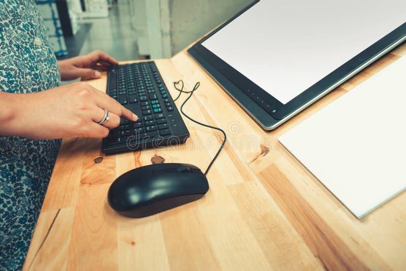 Las manos de la mujer del primer están utilizando el teclado para el uno mismo de los productos en el ordenador en grandes almace fotos de archivo
