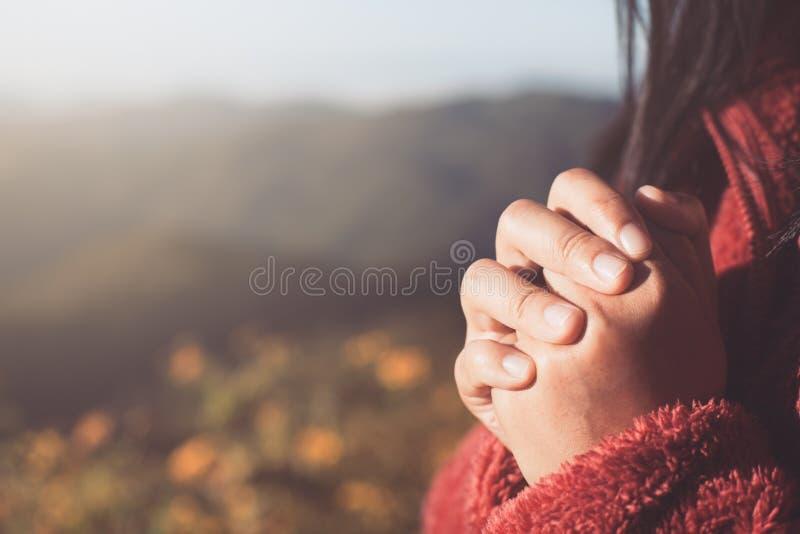 Las manos de la mujer doblaron en rezo en fondo hermoso de la naturaleza fotografía de archivo libre de regalías