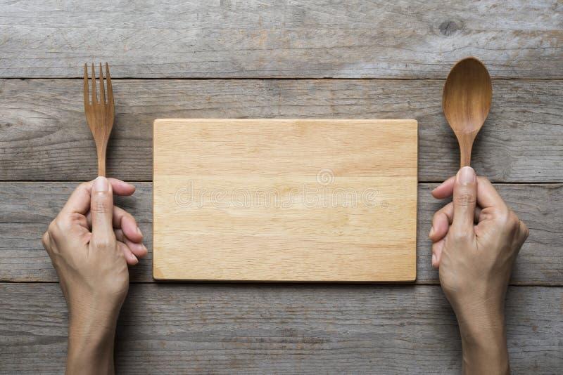 Las manos de la mujer dos sostienen un plato de la cuchara y de la bifurcación y de madera en el CCB de la tabla fotos de archivo