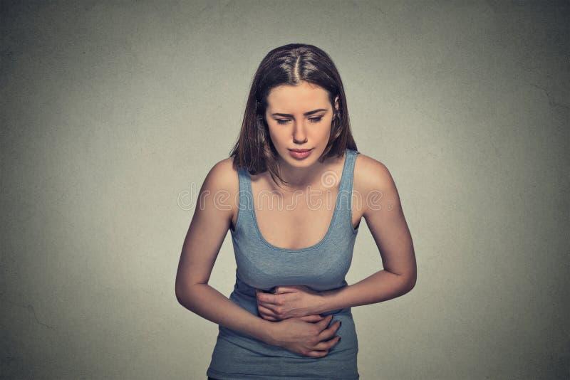Las manos de la mujer en el estómago que tiene malos dolores duelen imagen de archivo