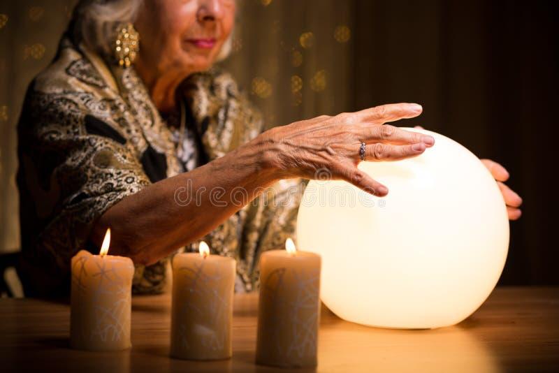Las manos de la mujer en la bola de cristal imagen de archivo libre de regalías