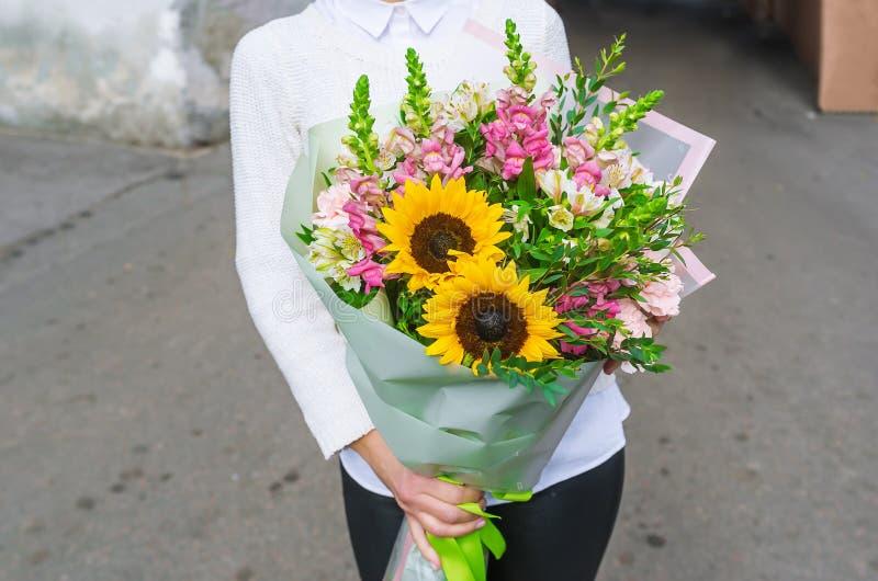 Las manos de la mujer están con un ramo bonito de girasoles amarillos hermosos fotografía de archivo