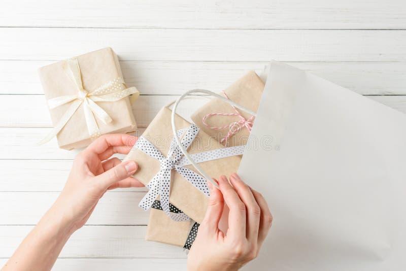 Las manos de la mujer están envolviendo presentes en un bolso del regalo en el fondo blanco, visión superior imagen de archivo