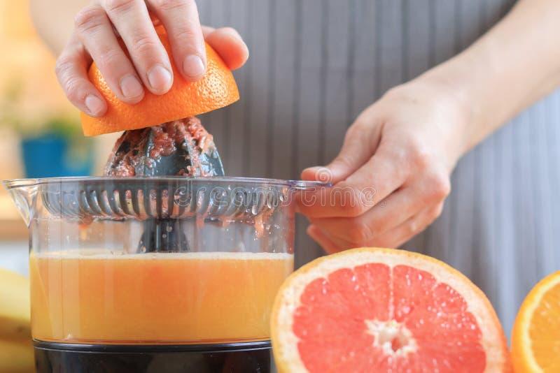Las manos de la mujer están llevando a cabo una mitad anaranjada y están haciendo el jugo imágenes de archivo libres de regalías