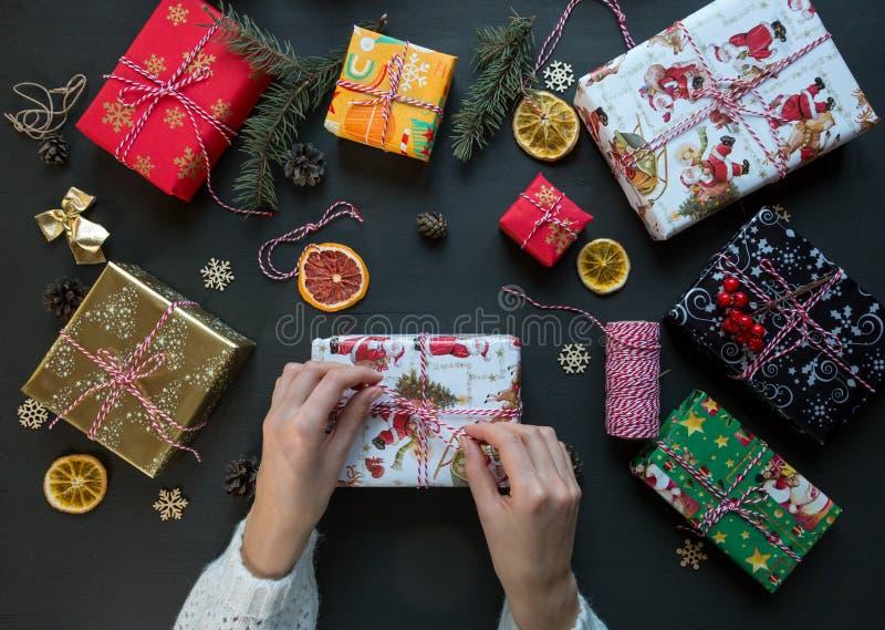 Las manos de la mujer hacen el arco en la caja de regalo en la tabla de madera negra alrededor de otros presentes La Navidad y Añ foto de archivo libre de regalías