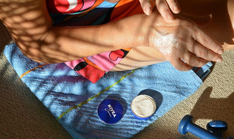 Las manos de la mujer manchan la crema del nivea foto de archivo libre de regalías