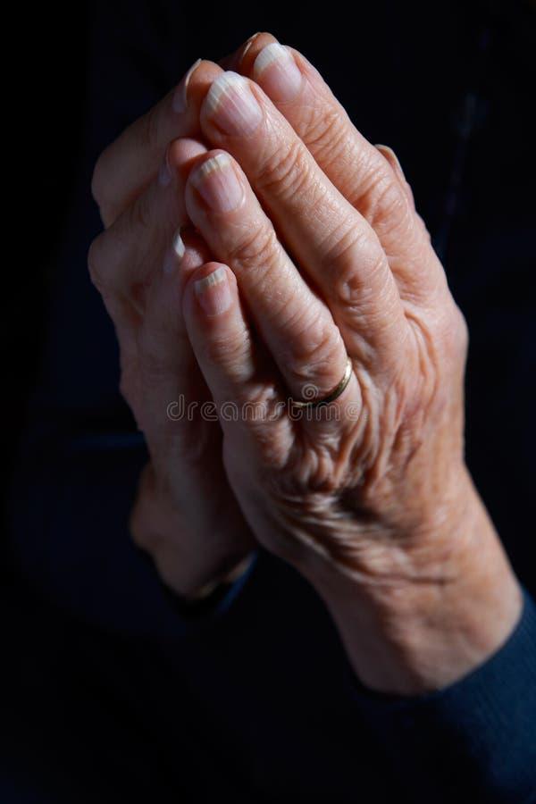 Las manos de la mujer mayor abrochadas en rezo foto de archivo
