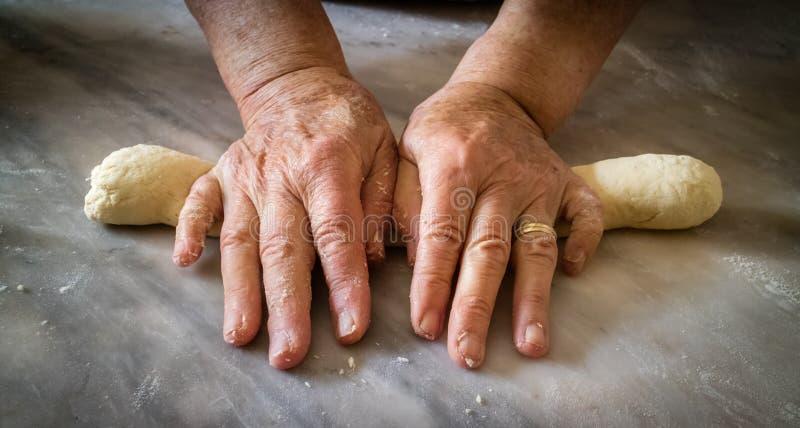 Las manos de la mujer mayor que amasan la pasta para hacer las bio pastas italianas frescas foto de archivo