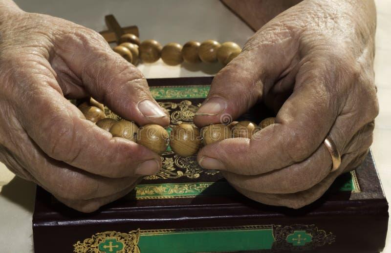 Las manos de la mujer mayor que sostienen el rosario imagen de archivo