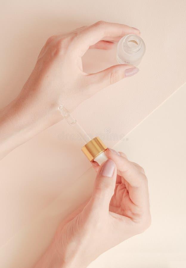 Las manos de la mujer preparada hermosa con el suero en un fondo ligero Aceite de alimentaci?n para la piel limpia y suave en inv imagen de archivo