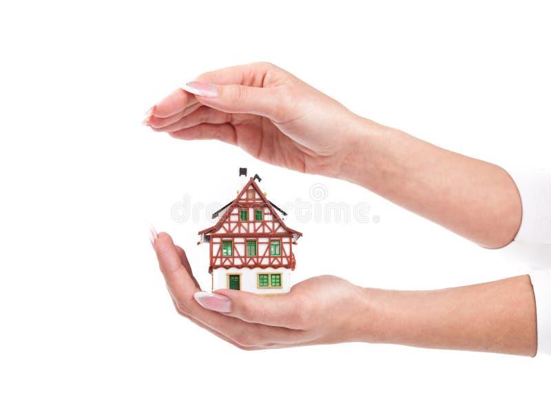 Las manos de la mujer protegen poca casa en blanco imágenes de archivo libres de regalías