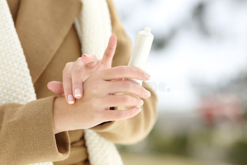 Las manos de la mujer que frotan la aplicación hidratan la crema en invierno imagen de archivo libre de regalías