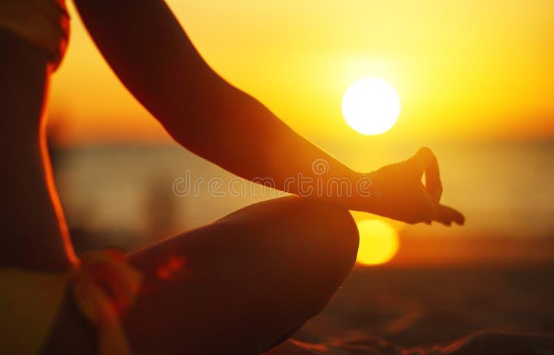 Las manos de la mujer que meditan en yoga presentan en la puesta del sol en la playa foto de archivo