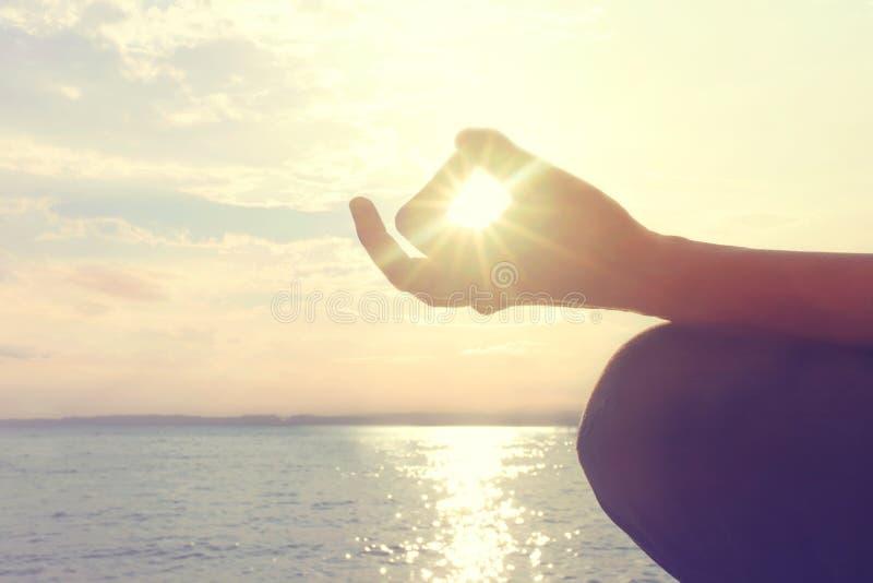 Las manos de la mujer que reflexionan sobre una yoga presentan en la playa fotos de archivo