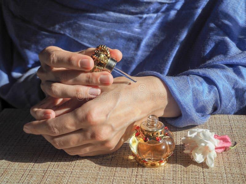 Las manos de la mujer que rocían perfume en su mujer oriental de la muñeca consiguen el aceite del perfume en sus muñecas fotografía de archivo libre de regalías
