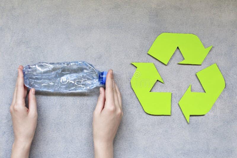 Las manos de la mujer que sostienen la botella plástica con reciclan símbolo en fondo gris imagen de archivo libre de regalías