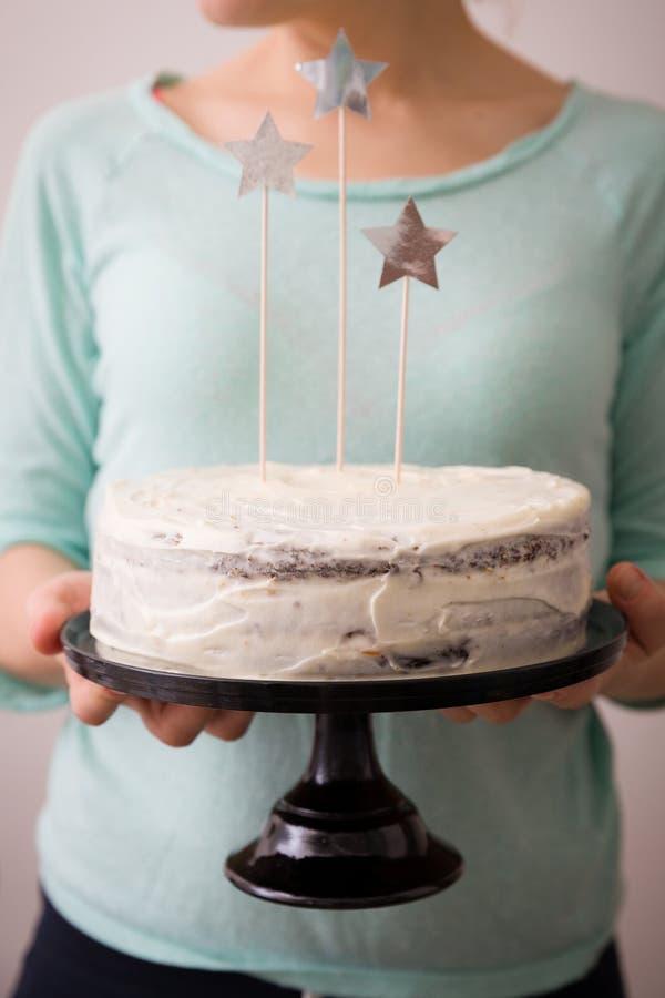 Las manos de la mujer que sostienen la torta blanca del cumpleaños hecho en casa delicioso adornada con las estrellas Fondo azul  imagen de archivo libre de regalías