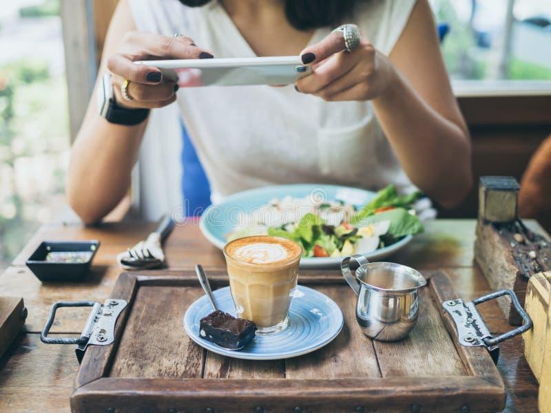 Las manos de la mujer que toman la foto de la taza de café en la tabla de madera por smartphone foto de archivo