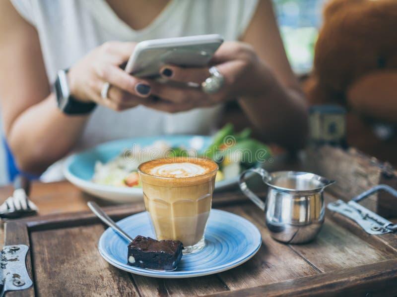 Las manos de la mujer que toman la foto de la taza de café en la tabla de madera por smartphone fotos de archivo libres de regalías