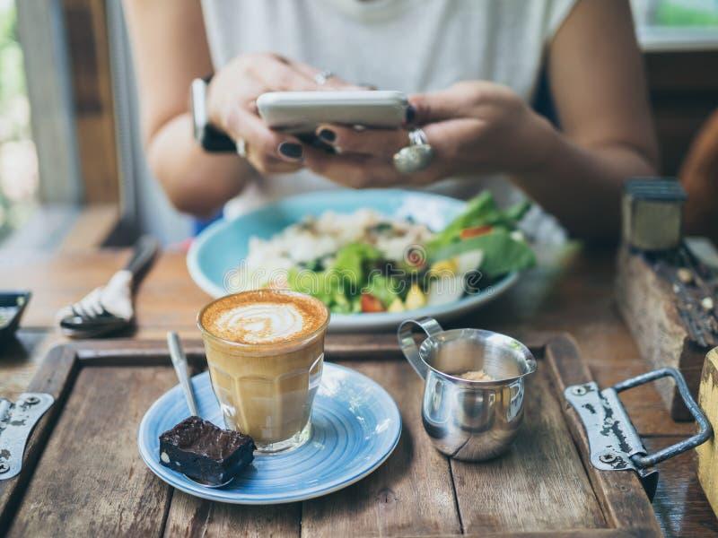 Las manos de la mujer que toman la foto de la taza de café en la tabla de madera por smartphone imágenes de archivo libres de regalías