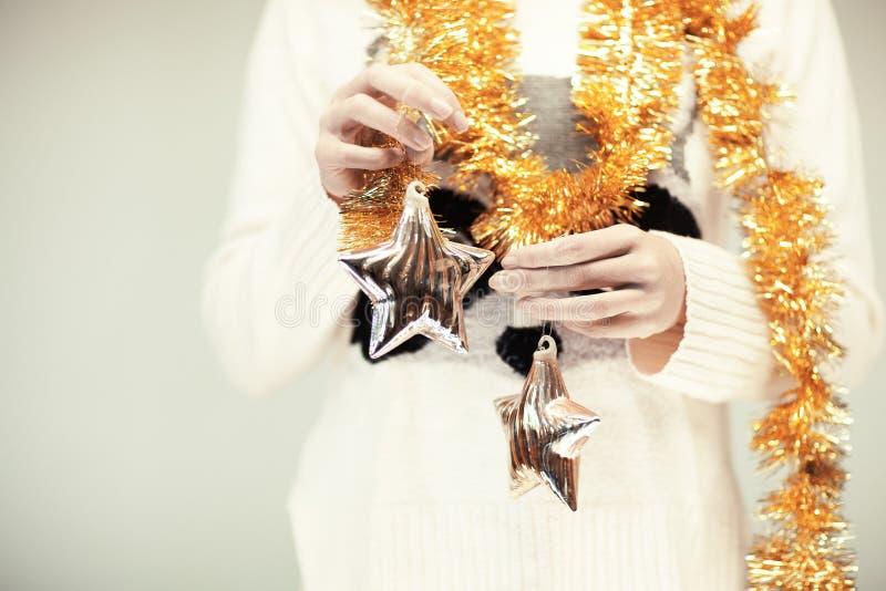 Las manos de la mujer se cierran encima de sostener las estrellas de la decoración de la Navidad fotografía de archivo